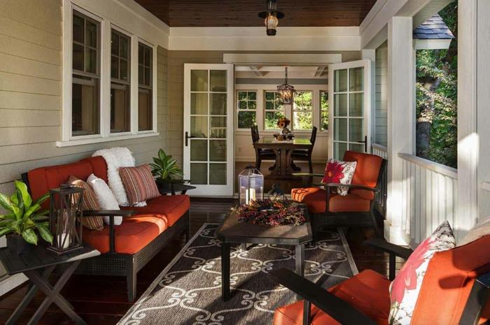 sofas en rouge et noir, tapis, table basse, veranda ouverte, portes accordéon blanches