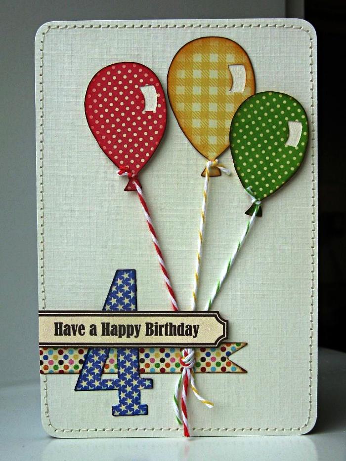 une carte anniversaire enfant en papier texturé décorée de petits ballons en papier cartonné à pois et à carreaux