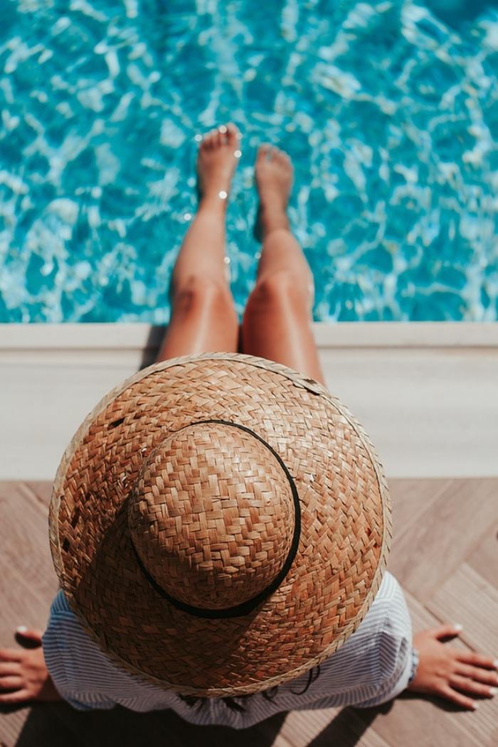 une jeune femme assisse au bord d'une piscine coque, les pieds dans l'eau bleu