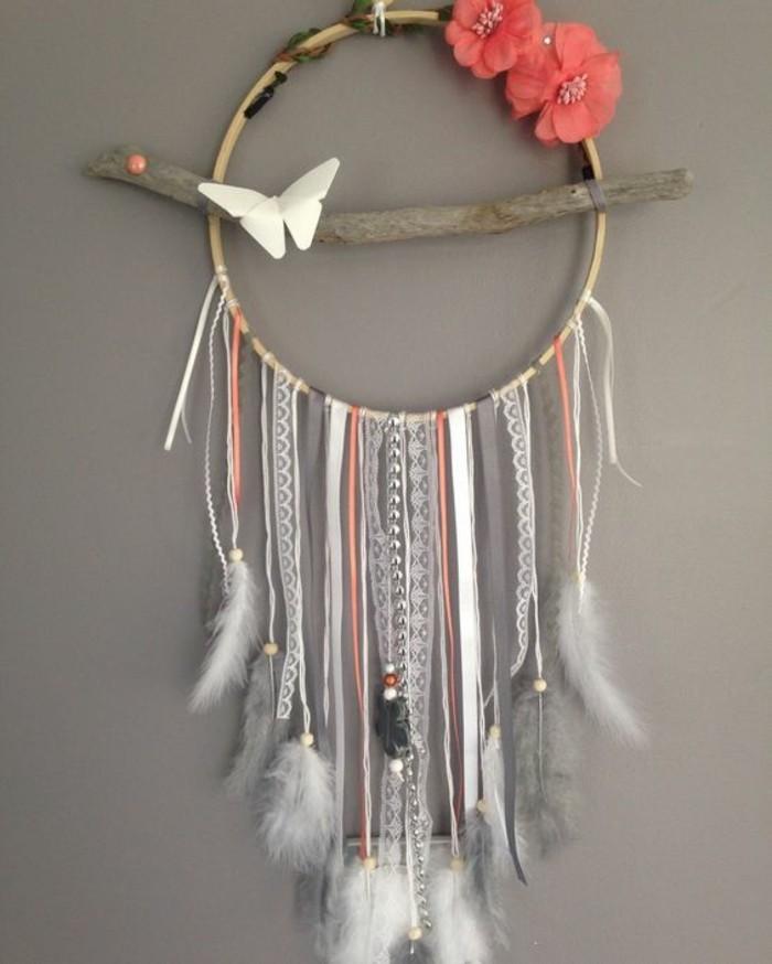 attrape-rêve, cerceau en bois et franges suspendues, bâton en bois flotté, mur gris