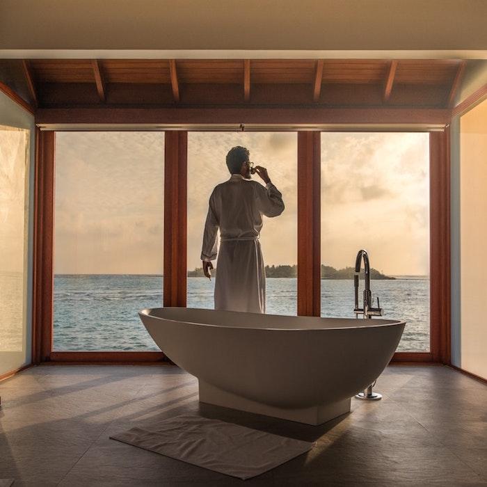 Homme qui boit son café dans la salle de bain avec baignoire et porte fenetre vue de l'ocean
