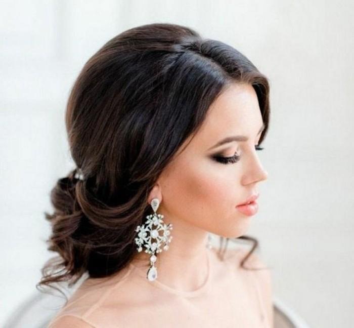 chignon bas avec des boucles et volume sur le dessus, raie au milieu, mèches libres autour de la tête, coiffure de mariée originale