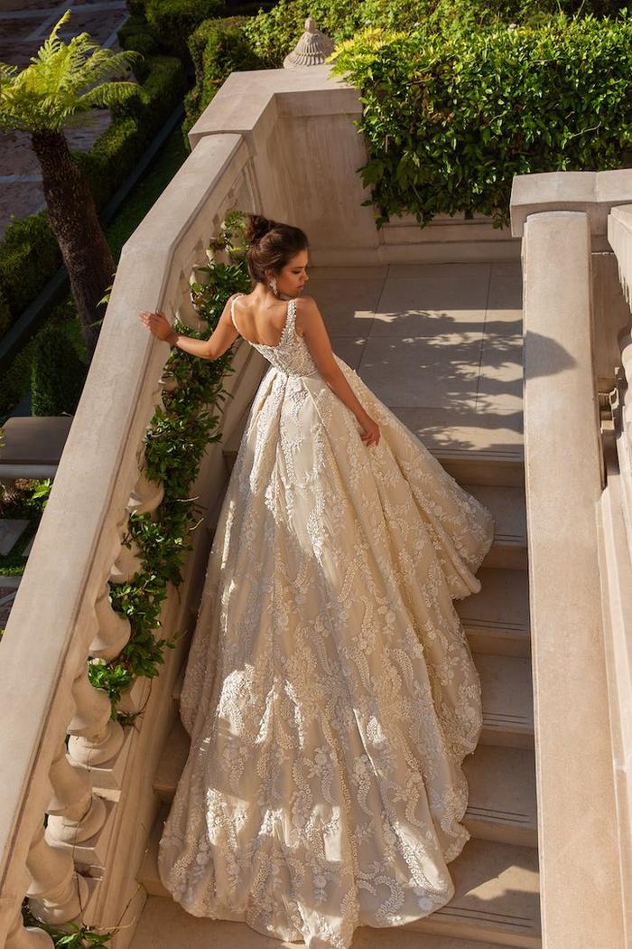 Longue robe de mariée bustier princesse avec longue traine, belle femme en blanc robe dentelle photo sur les escaliers d'une résidence