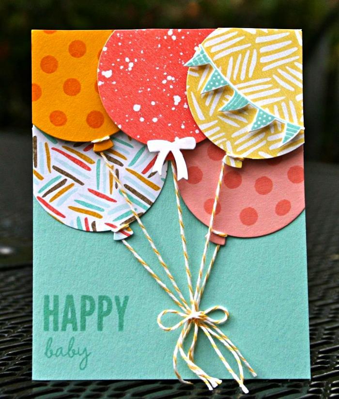 une carte anniversaire 1 an couleur vert d'eau, décorée de ballons en papier cartonné imprimé noués avec des ficelles