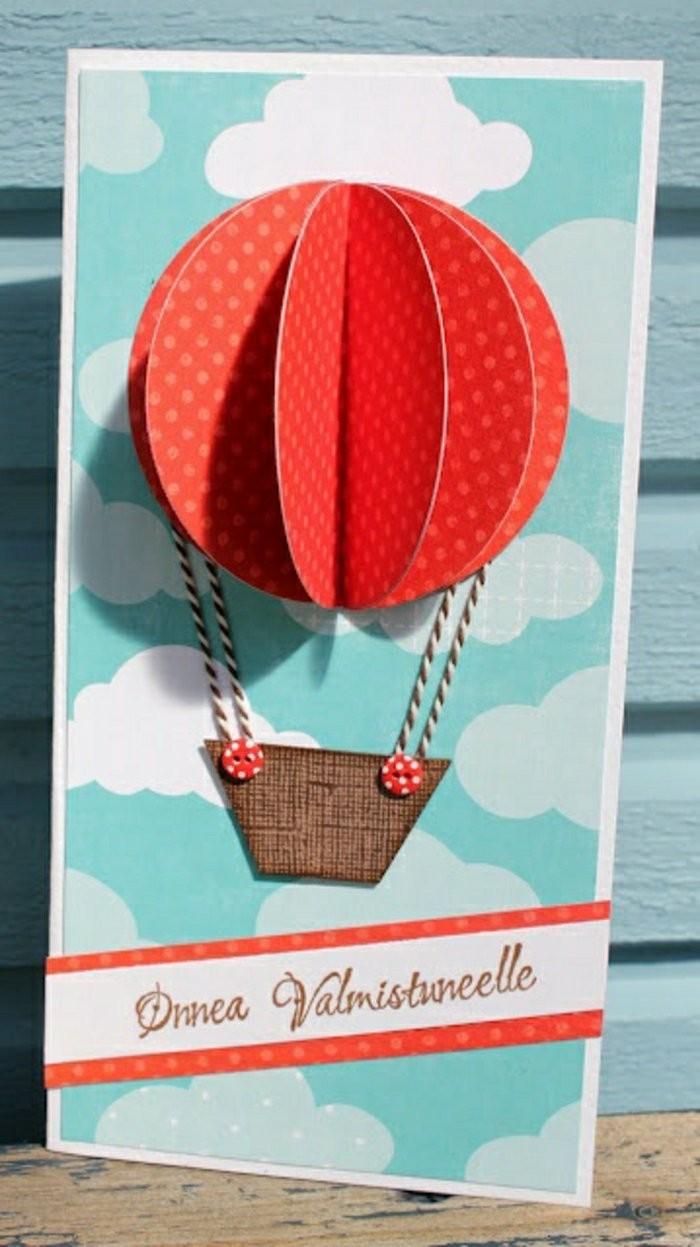 carte anniversaire 1 an en papier imprimé motifs nuages, ornée de montgolfière en relief en papier cartonné