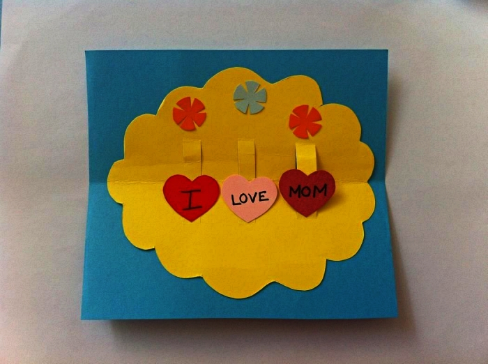 une carte pop-up à fabriquer avec les enfants à l'école maternelle, carte pour la fête des mères avec petit mot doux écrit sur coeurs en papier
