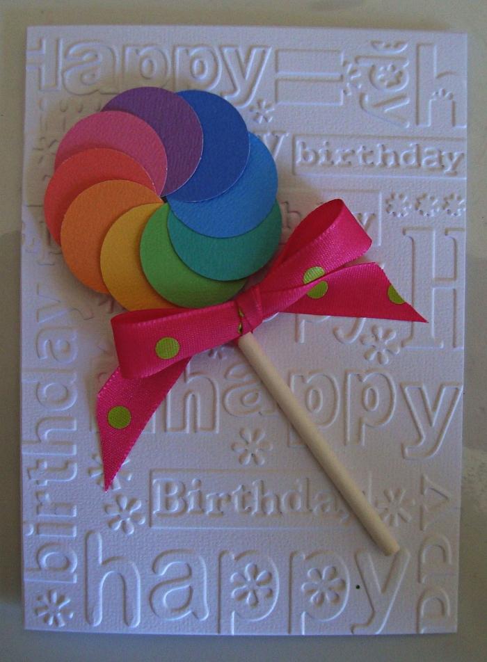 carte anniversaire 1 an en papier blanc embossé décorée d'une sucette en papier cartonné aux couleurs de l'arc-en-ciel