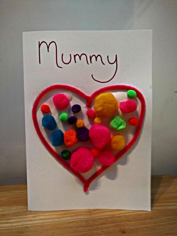 activité manuelle facile 3-5 ans à l'occasion de la fête des mères, carte avec cœur en cuire-pipe et des pompons colorées à l'intérieur