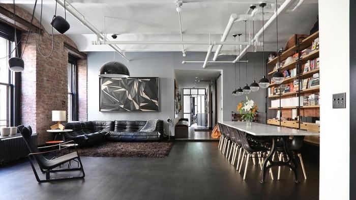 meuble style industriel dans un salon gris, modèle de canapé en cuir noir, éclairage industriel sur rail en blanc mate