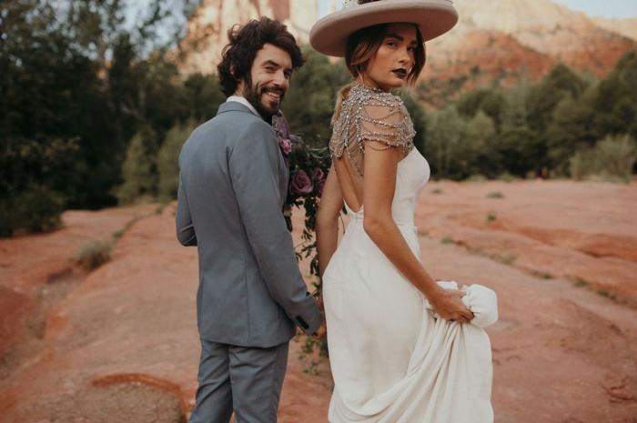 chapeau tendance beige, costume gris, épaules en bijoux, dos nu, tatouage, rouge à lèvres foncé