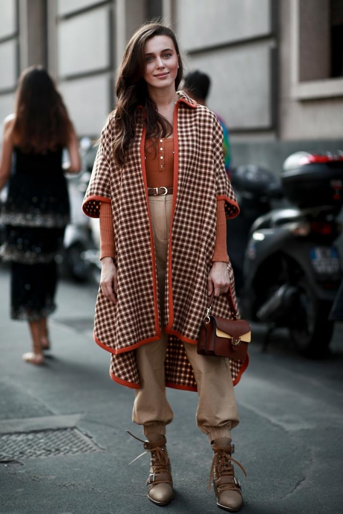 manteau cape aux motifs géométriques, pantalon beige, bottes beiges, chemise orange