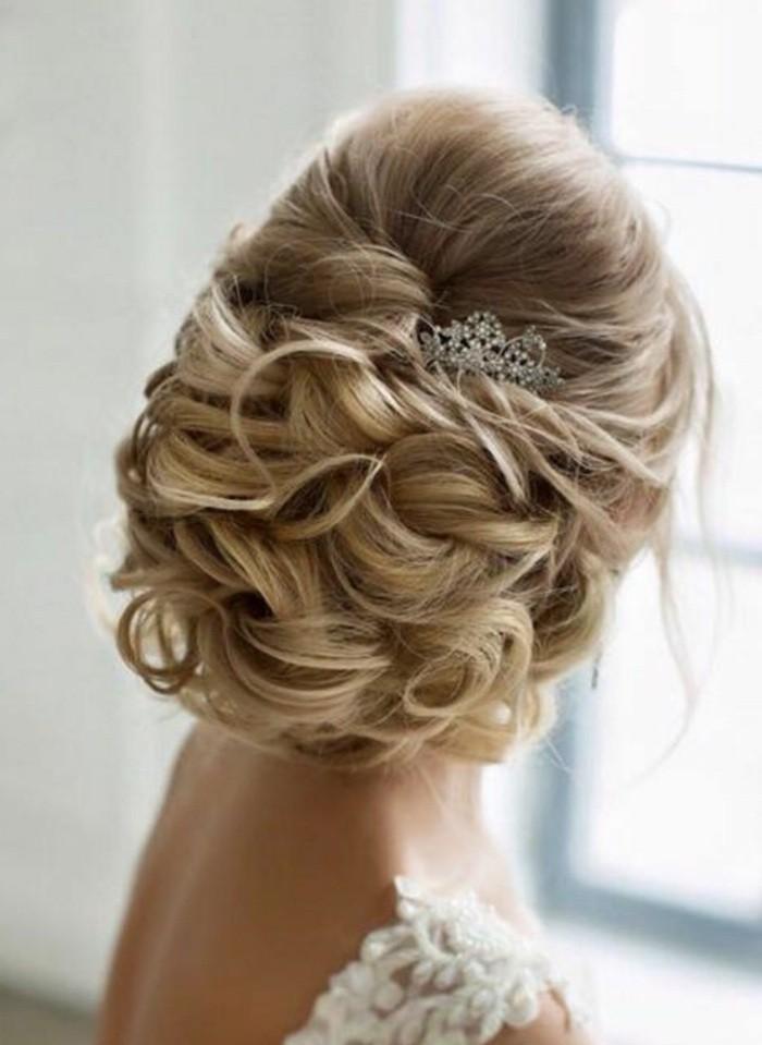 chignon bas bouclé sur cheveux blond, modele de cheveux en volume accessoirisés d un bijou pour cheveux