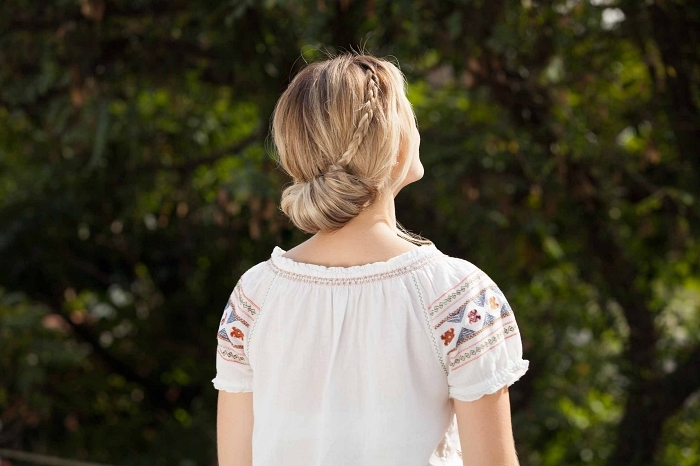 idée de coiffure femme pour l'été, chignon bas enroulé avec petite natte sur le côté sur cheveux longs blond