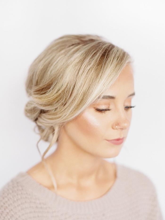 vue de front sur un chignon tressé bas décoiffé, coiffure femme blonde avec volume sur le dessus et quelques mèches libres