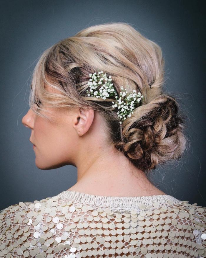 coiffure mariage chignon torsadé bas accessoirisée de fleurs, chignon coiffé décoiffé volumineux qui met en valeur les cheveux ondulés