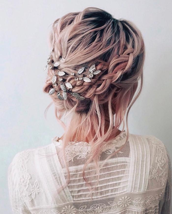 chignon coiffé décoiffé avec tresse floué sur le côté, accessoirisé avec une broche à motifs floraux, coiffure à inspiration bohème chic sur cheveux rose gold