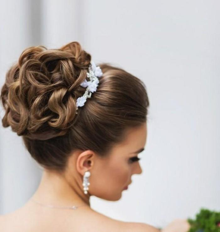 chignon haut aux boucles entouré d une petite couronne de fleurs blanches, chignon mariage élégant