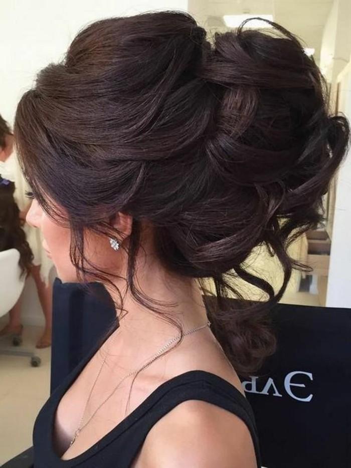 coiffure mariage ultra volumineuse avec un chingnon xxl aux boucles et mèches tombantes, volume sur le dessus