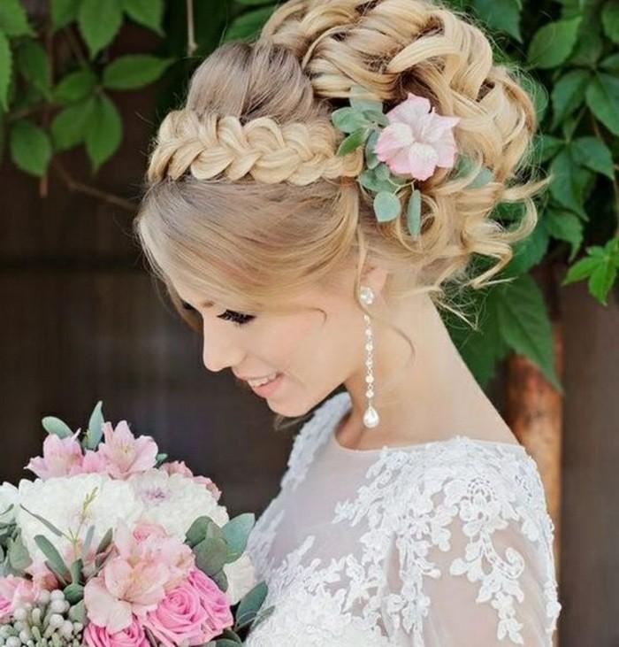 coiffure mariage chignon bouclé avec tresse sur le front et volume sur le dessus, accessoire pour cheveux fleur rose, robe de mariée dentelle