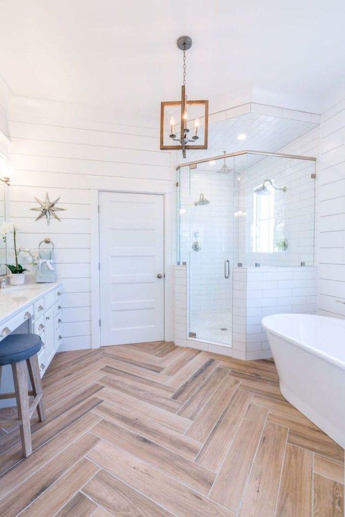Baignoire salle de bain scandinave, salle de bain en bois et blanc, lustre avec bougies, sol plancher simili en granite