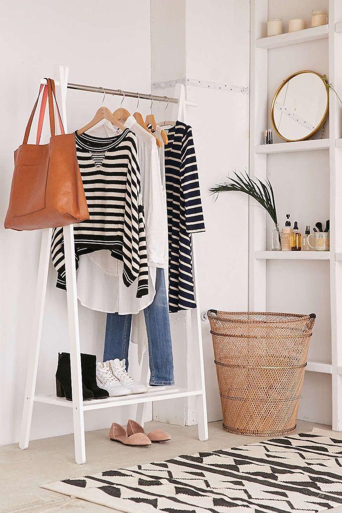 Rangement vêtements tapis noir et blanc, miroir ronde, vêtements blanc et noir, idée rangement chambre, aménagement chambre à coucher moderne