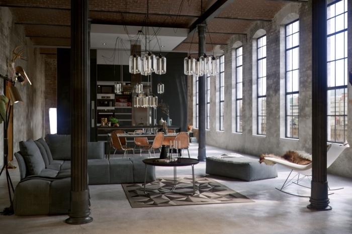 aménagment loft industriel aux murs béton avec canapé gris anthracite et petite table métal, idée chaise style industriel