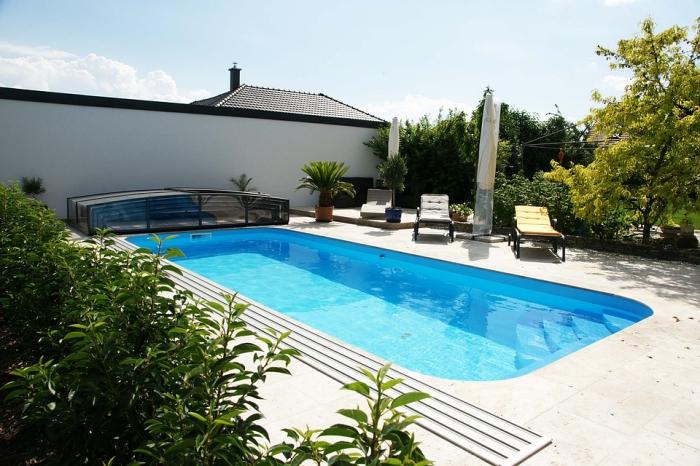 une piscine coque rectangulaire avec plage en travertin beige clair aménagée dans l'arrière-cour et entourée de verdure