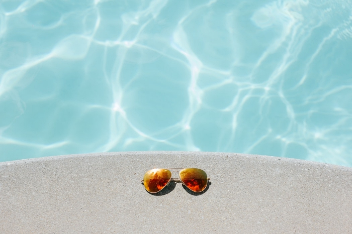 une paire de lunettes de soleil posées sur le bord en béton d'une piscine