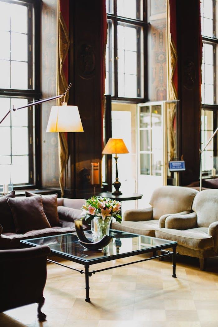 Beau salon moderne décoré au style industriel, lampe sur la table ronde, table basse en verre avec vase de fleurs en haut