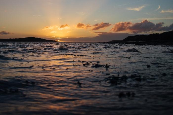 fond ecran ete, idée paysage romantique au bord de la mer, photo ciel doré avec nuages et rayons du soleil
