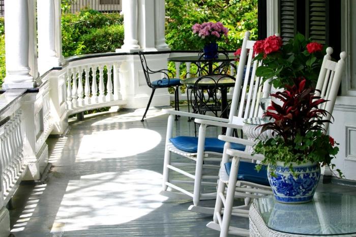 terrasse blanche, chaises balançantes blanches, pot de fleur style marin, plantes fleuries, table en fer forgé