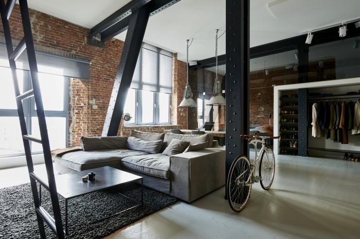 agencement espace loft industriel aux murs briques rouges avec meuble style industriel, modèle de canapé d'angle