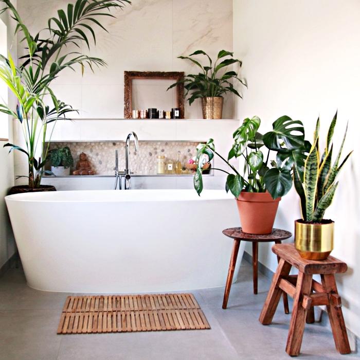espace baignoire zen et naturelle décoré de plantes vertes, une niche murale revêtue de carrelage galets, amenagement salle de bain ambiance zen et nature