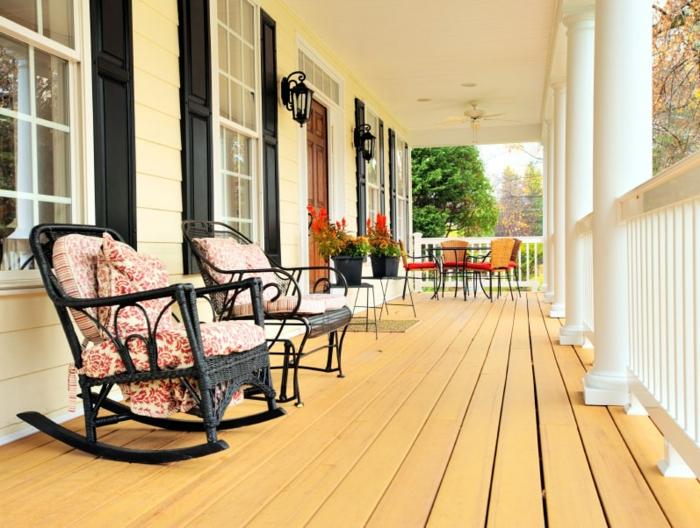 chaises de relaxation sur une terrasse en bois, grande véranda ouverte en bois et blanc, rambarde blanche