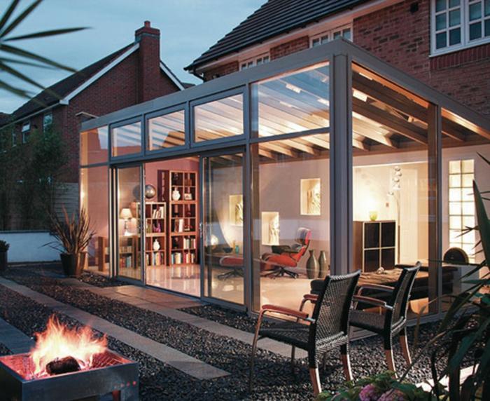 agrandissement de maison contemporaine, véranda équipée et vitrée, chaises de jardin, cheminée ouverte