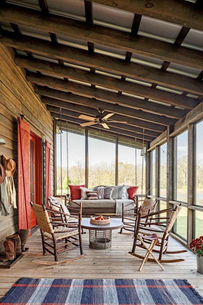 veranda tout bois, volets de fenêtre peints rouges, sofa gris, lampe ventilateur, tapis rayé au sol en bois