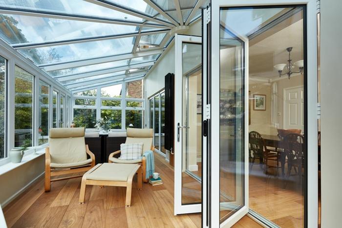 comment amenager une veranda avec style, porte accordéon, toiture vitrée, chaises en bois et textile beige, table basse