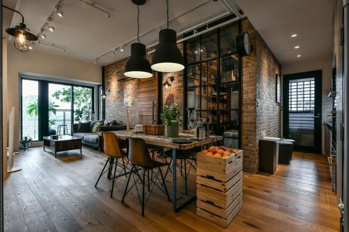 exemple de déco industrielle salon ouvert, pièce aux murs briques avec parquet bois foncé, éclairage sur rail blanc mate