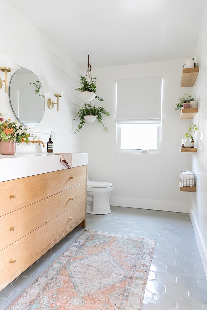 Plantes vertes decoration petite salle de bain, une salle de bain moderne, miroir ronde, meuble avec placards en bois et marbre blanche pour le lavabo