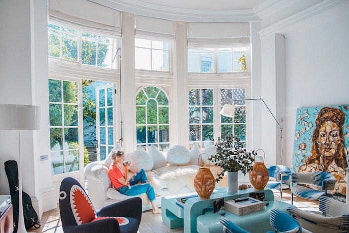 Salle de séjour moderne arrondie, beau canapé blanc de grande taille, peinture de femme pour décoration murale