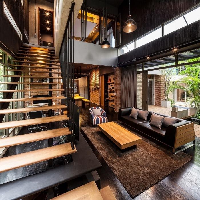 aménagement salon industriel au plafond haut noir avec parquet bois foncé, modèle de canapé en cuir noir décoré avec coussins gris