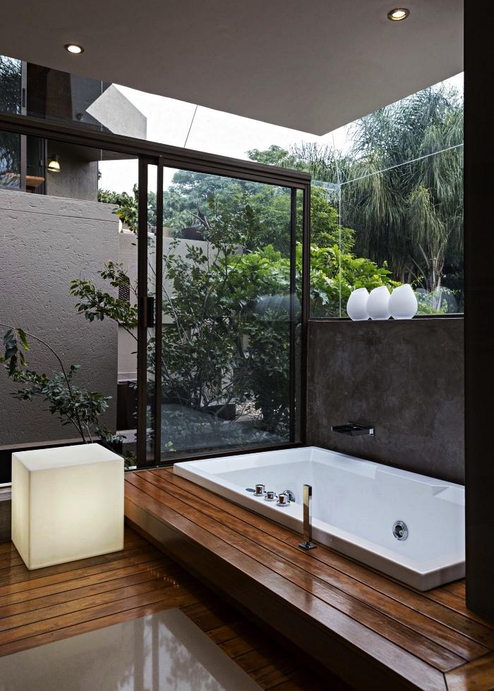 salle de bain zen avec larges baies vitrées et baignoire balnéo sur un plancher surélevé, modèle salle de bains japonaise