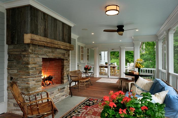 décorer sa terrasse et amenager une veranda chaleureuse, grande cheminée en pierre sofa bleu, plantes fleuries