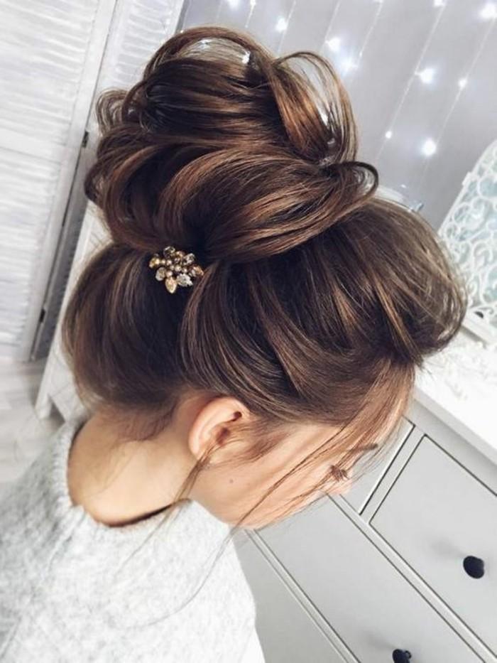 chignon coiffé décoiffé avec des mèches rebelles et gros volume, accessoire cheveux fleur bijou, coiffure boheme femme