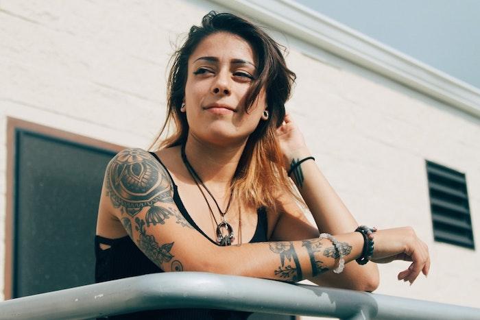 Femme au balcon, tatouages old school sur la main, tatouage main et épaule, dessin effectué sur la peau