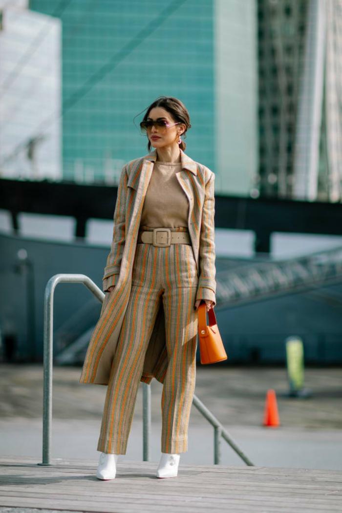 pantalon rayé en beige et jaune, longue veste rayée, lunettes oversize, petit sac orange, pantalon femme chic