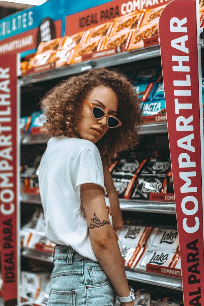 Fille cheveux crépus, jean bleu et top blanc dans le super marché idée tatouage graphique moderne, tatouage main, cool tatouage