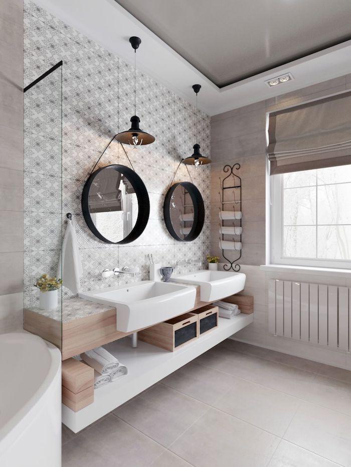 Deux miroirs rondes, carrelage à motif, boites rangement, tendance salle de bain en bois et blanc moderne au style scandinave