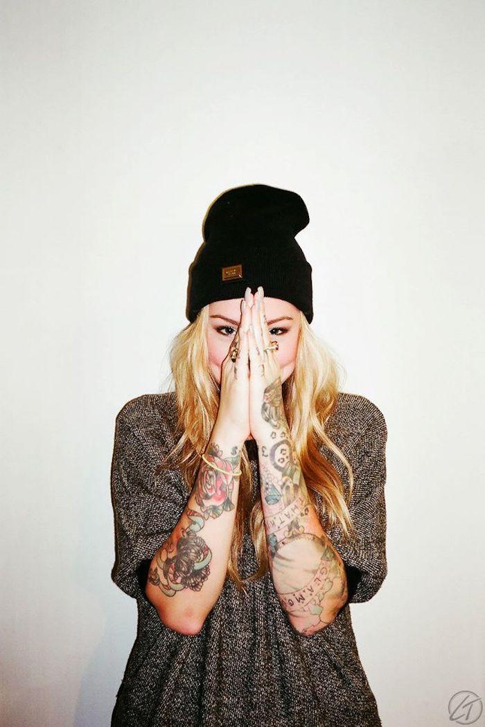 Fille swag tatouée avec des tatouages old school sur les deux mains, beanie sur cheveux blondes, longue tee shirt, tatouage avant bras, tatouage old school, inventer le design de son tatouage