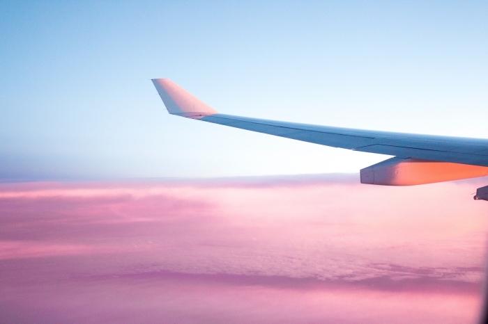 photo vol en avion avec ciel bleu et nuages roses, fond d écran magnifique pour wallpaper ordinageur sur le thème voyage